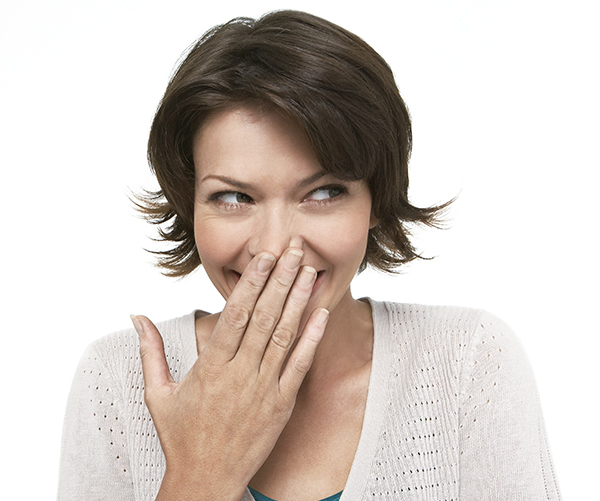 Woman with hand over her mouth, smiling